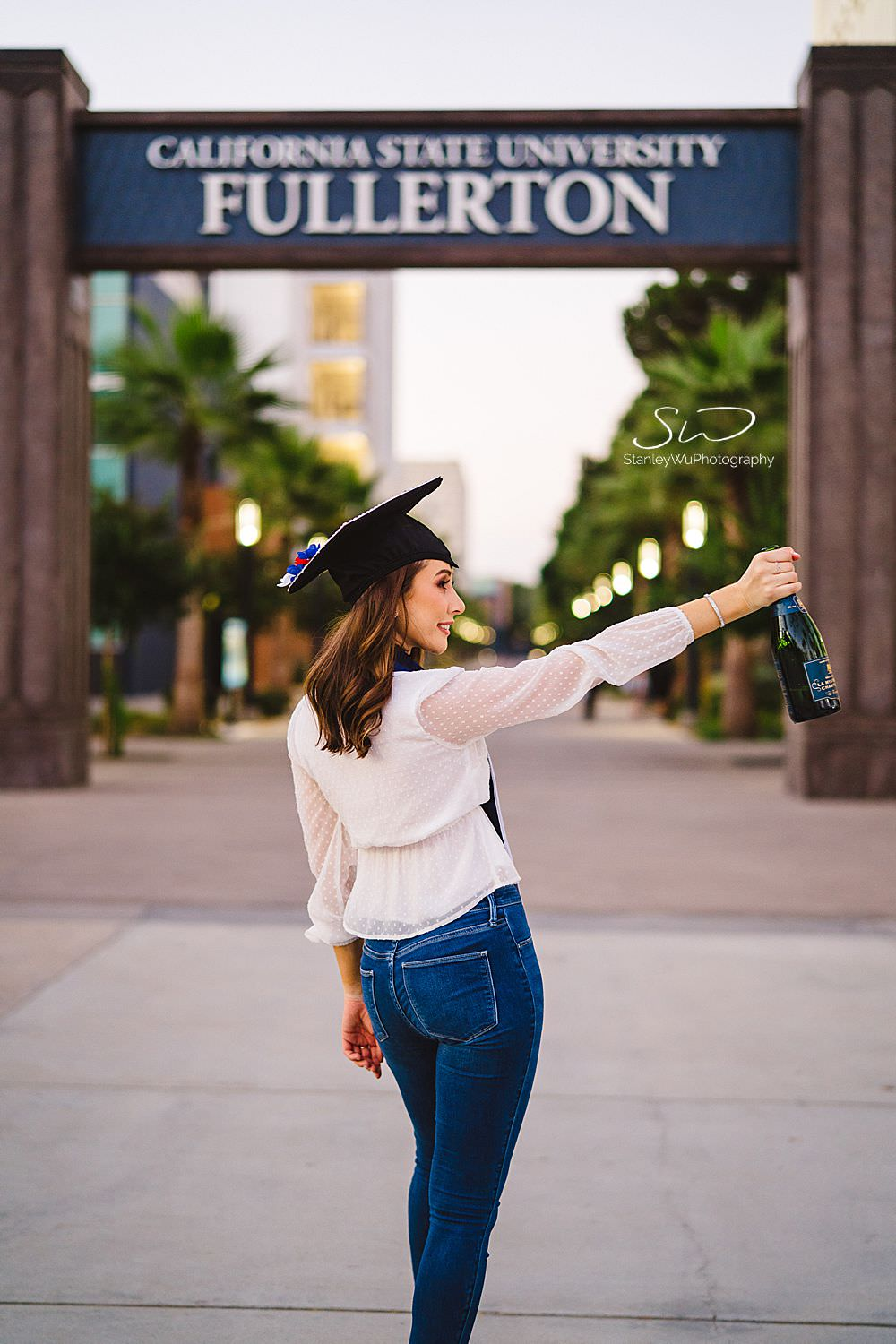 csu fullerton graduation photos popping champagne in front of the sign