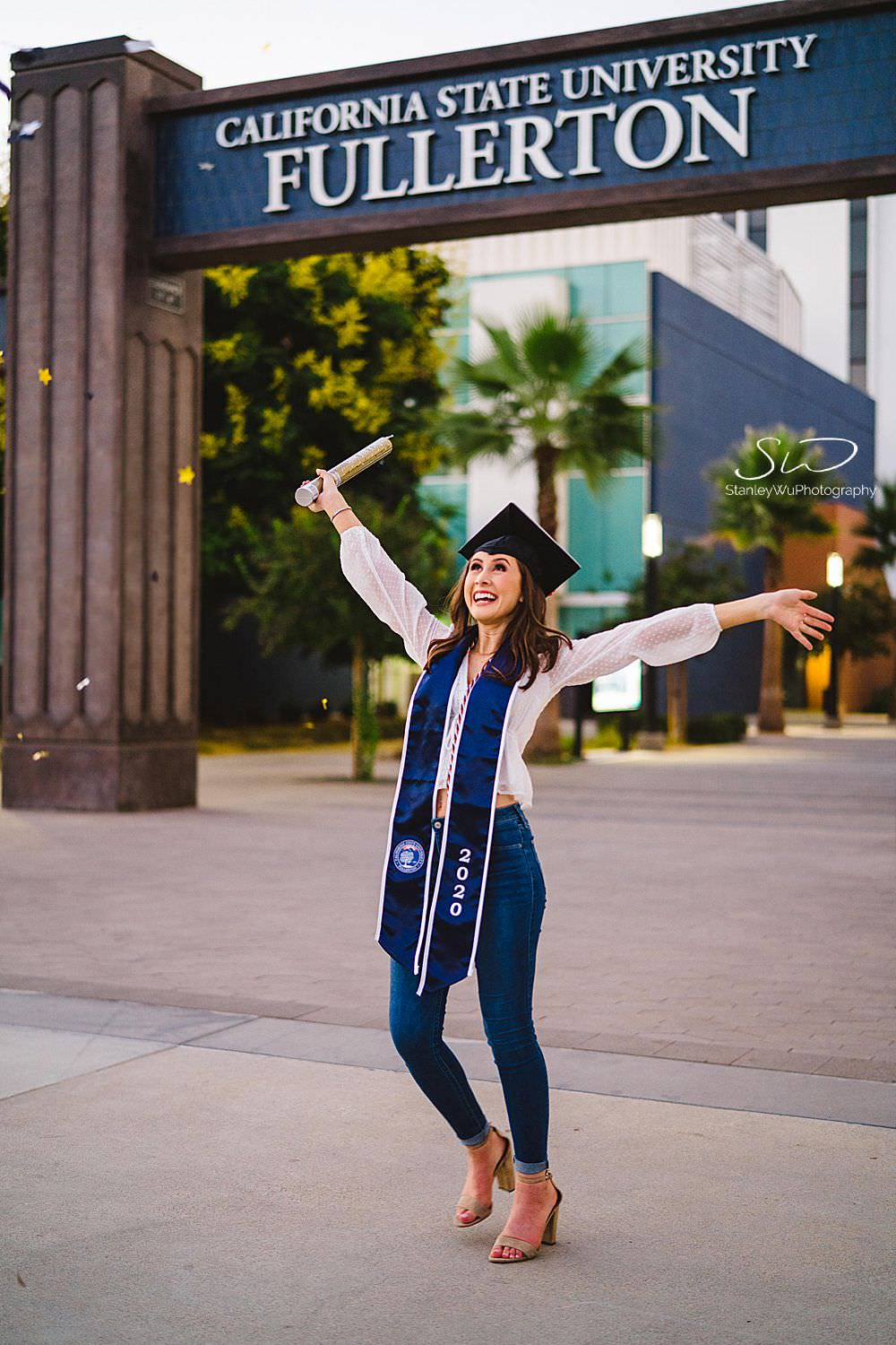 csu fullerton graduation photos playing with confetti in front of sign