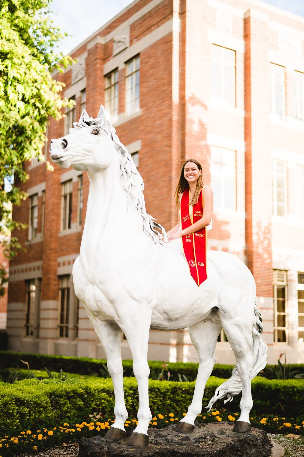 graduating senior sitting on traveler the horse statue usc mascot | usc graduation photographer los angeles